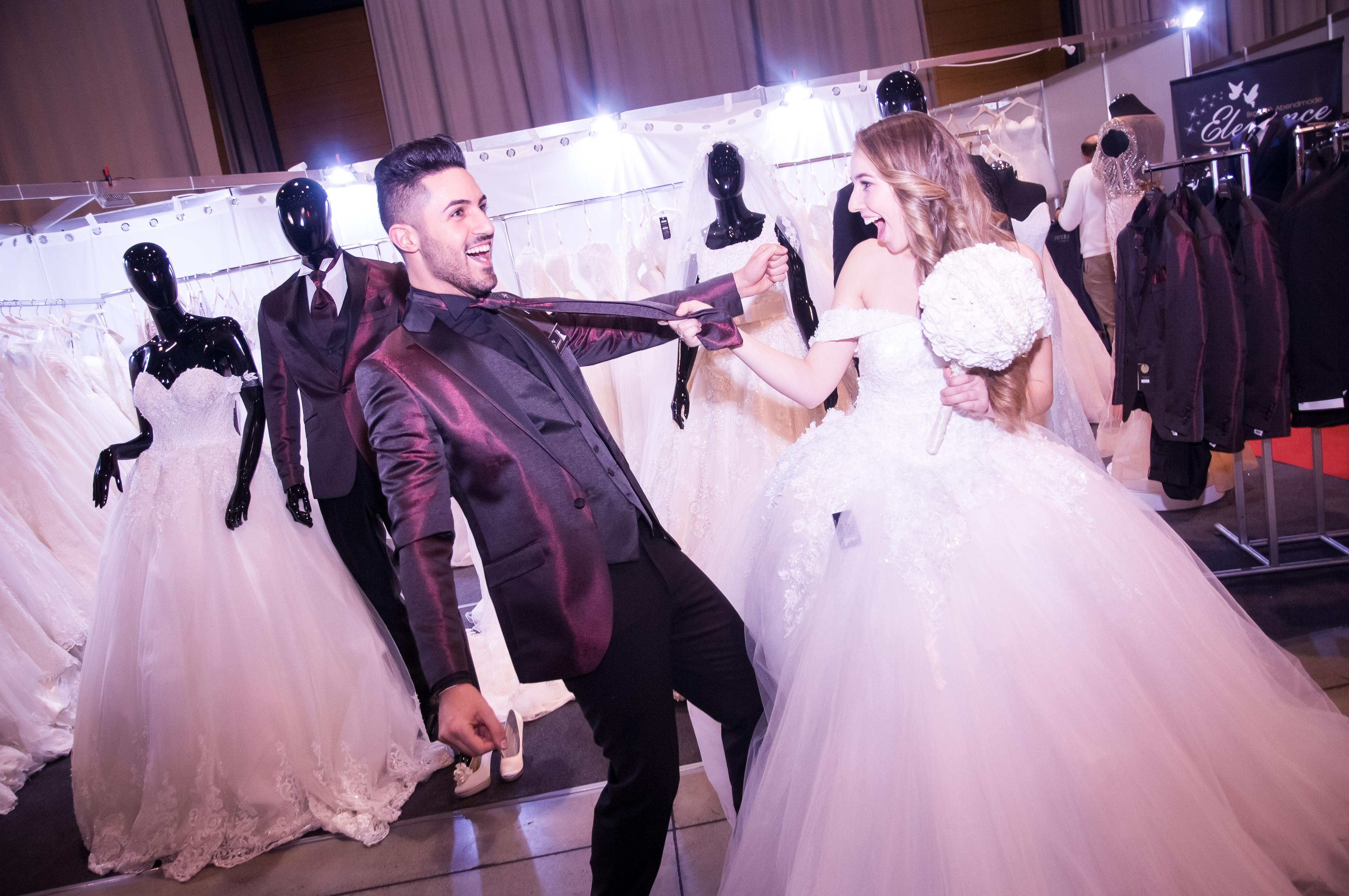 Na hier hat die Braut den Bräutiugam im Griff. Die Braut zieht dem Bräutigam an der Krawatte. Beide haben ihren Spass dabei. Fröhliche Stimmung.