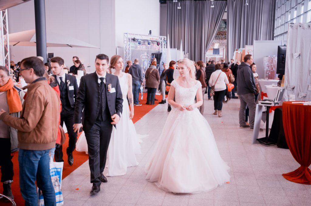 Besucher und Braut-Model auf der Hochzeitsmesse Trau gehen über die Messe und Bestaunen die Messestände.