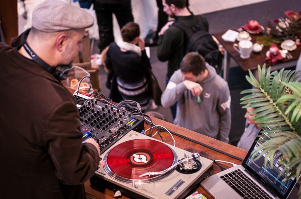Tanzende Besucher der Hochzeitmesse. Ein DJ legt Platten am Plattenspieler auf. Ein Hingucker der Hochzeitfeier.