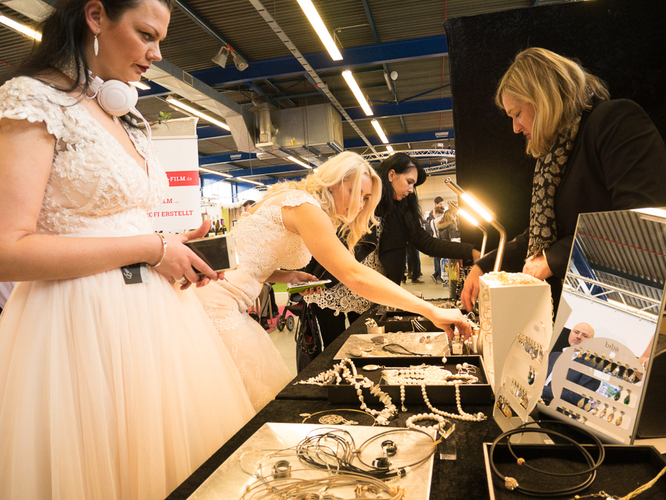 Braute suchen Schmuck für Ihre Hochzeit am Messestand aus. Probieren ihn an.